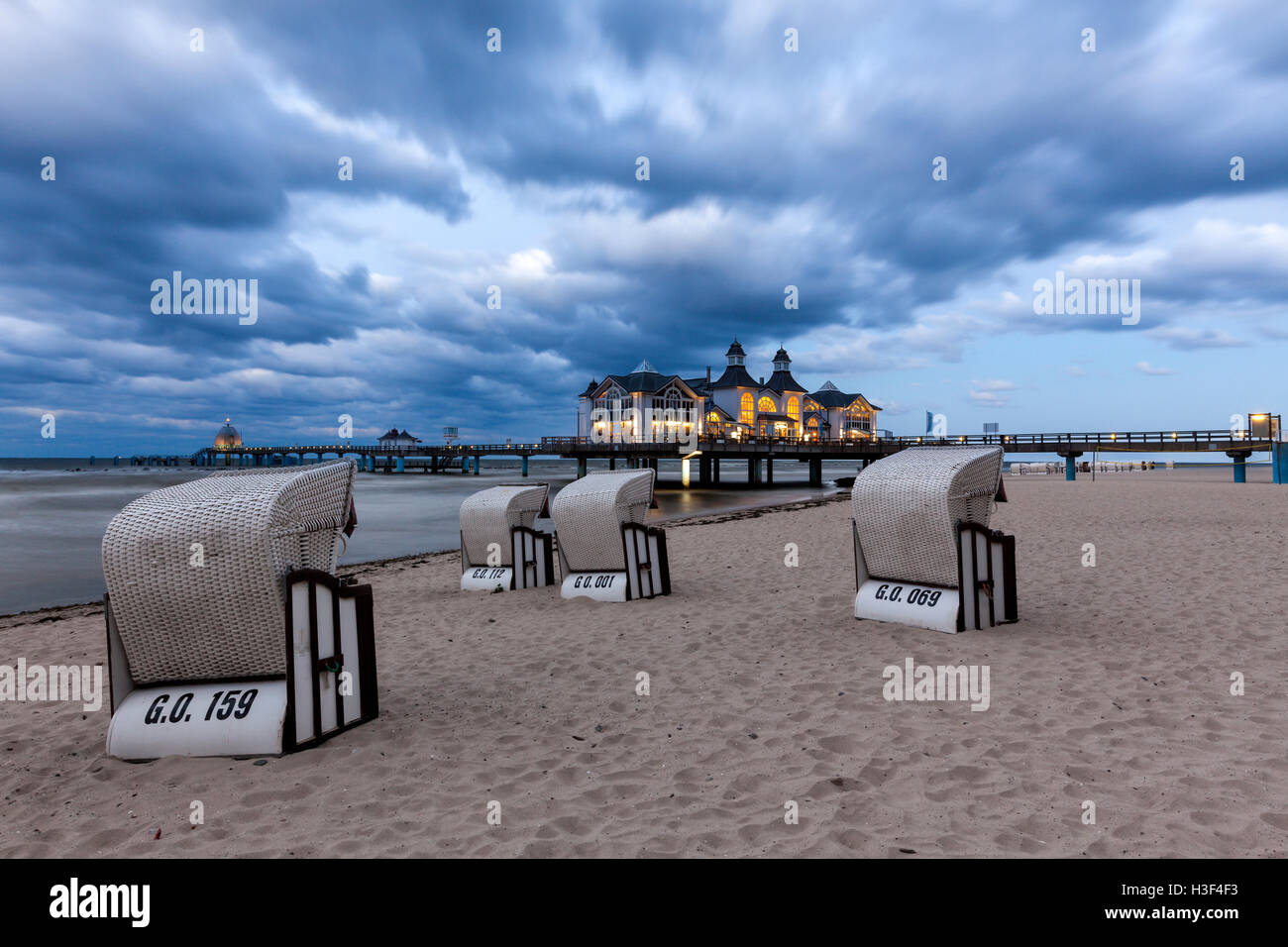 Beach chairs in front of the illuminated pier of Baltic Sea resort Sellin, Ruegen, at dusk - Stock Image
