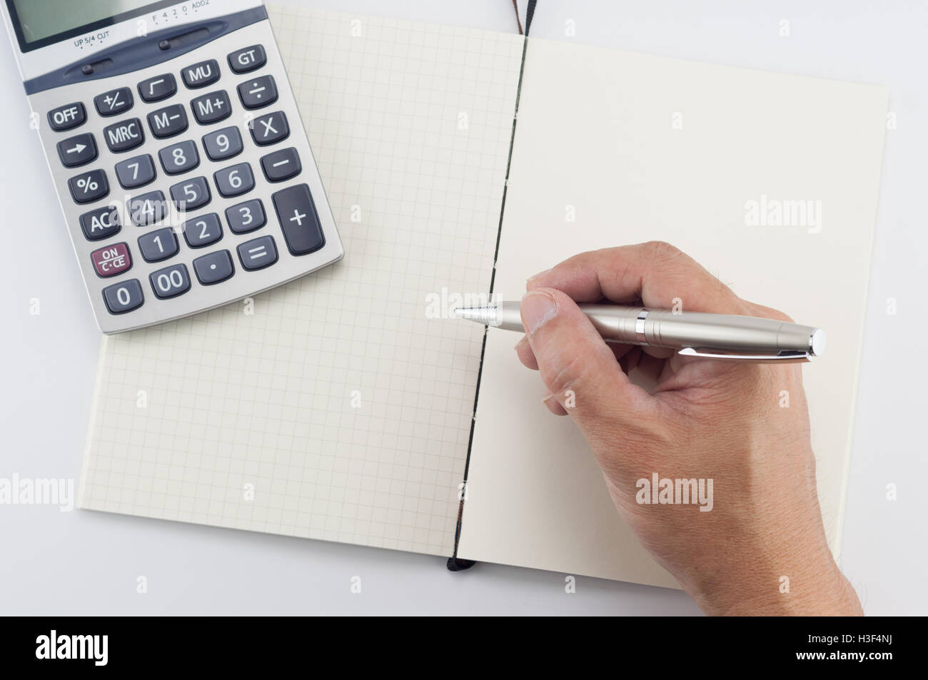 Man hand with pen writing on notepad, on white background. Stock Photo