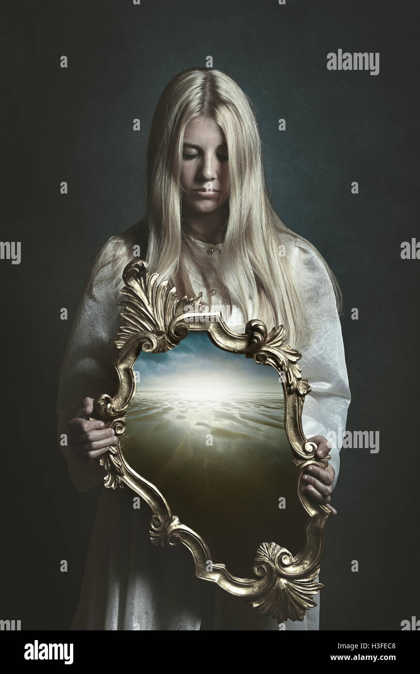 Woman holding magical mirror. Imagination and surreal - Stock Image