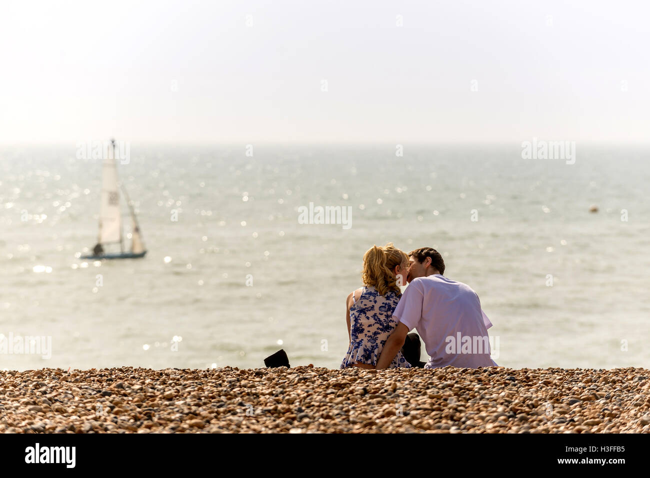 A young couple kissing on Brighton beach - Stock Image