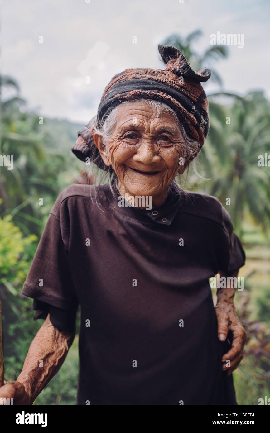 Portrait of old woman standing outdoors and smiling at camera. Senior female with beautiful smile on her face. - Stock Image