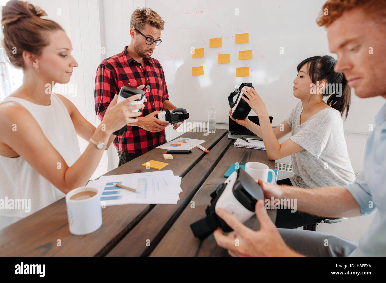 Group of young developers working on improving augmented reality devices. Diverse business team in meeting room - Stock Image