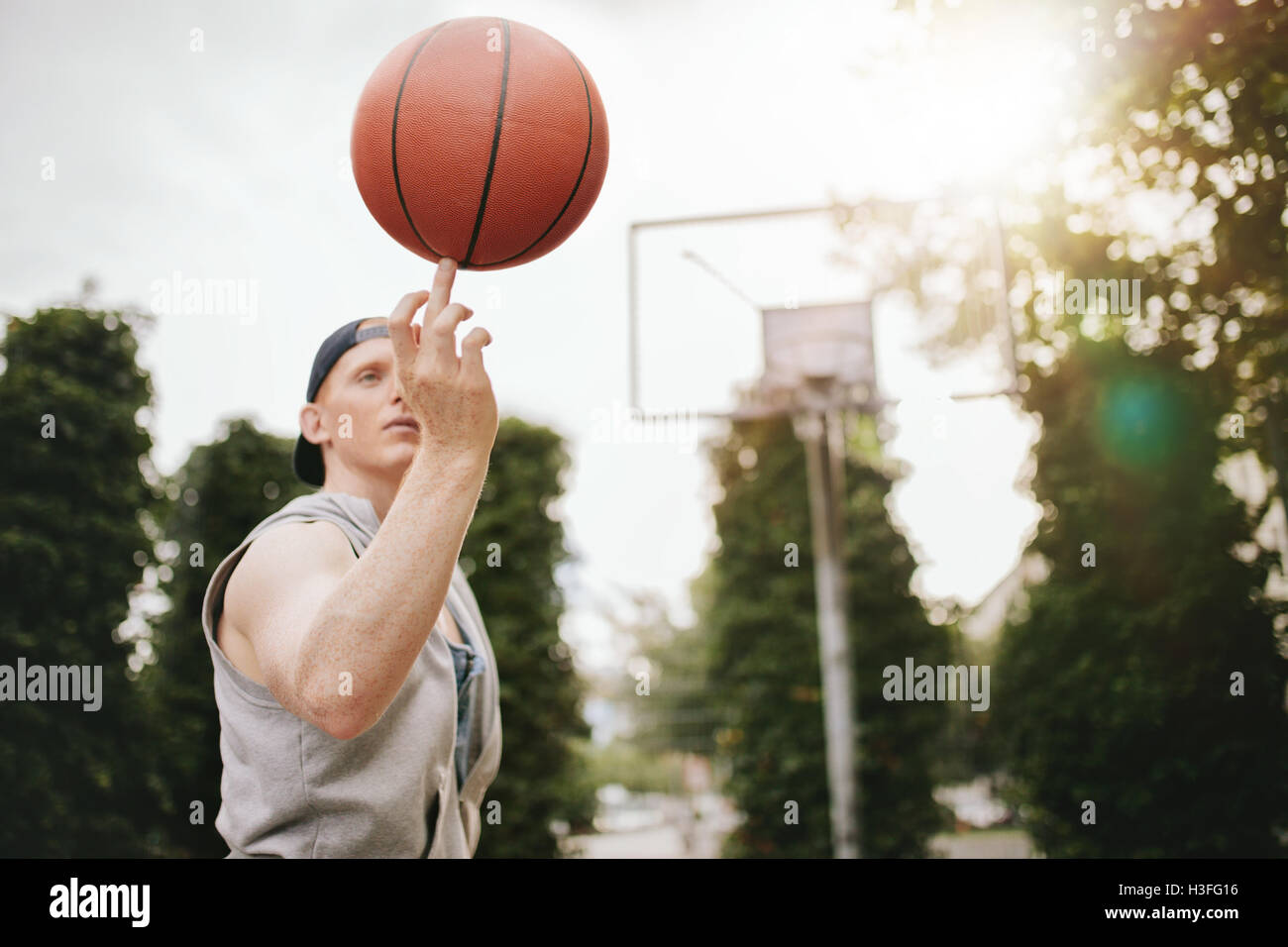 Young man balancing basketball on his finger on outdoor court. Streetball player spinning the ball. Focus on basketball. - Stock Image