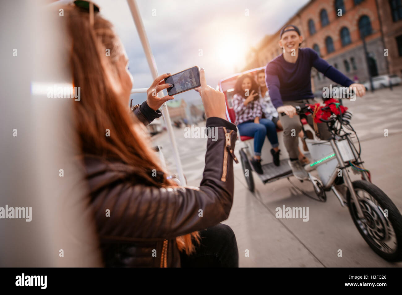 Female taking photographs of friends on tricycle ride. Friends enjoying vacation. - Stock Image