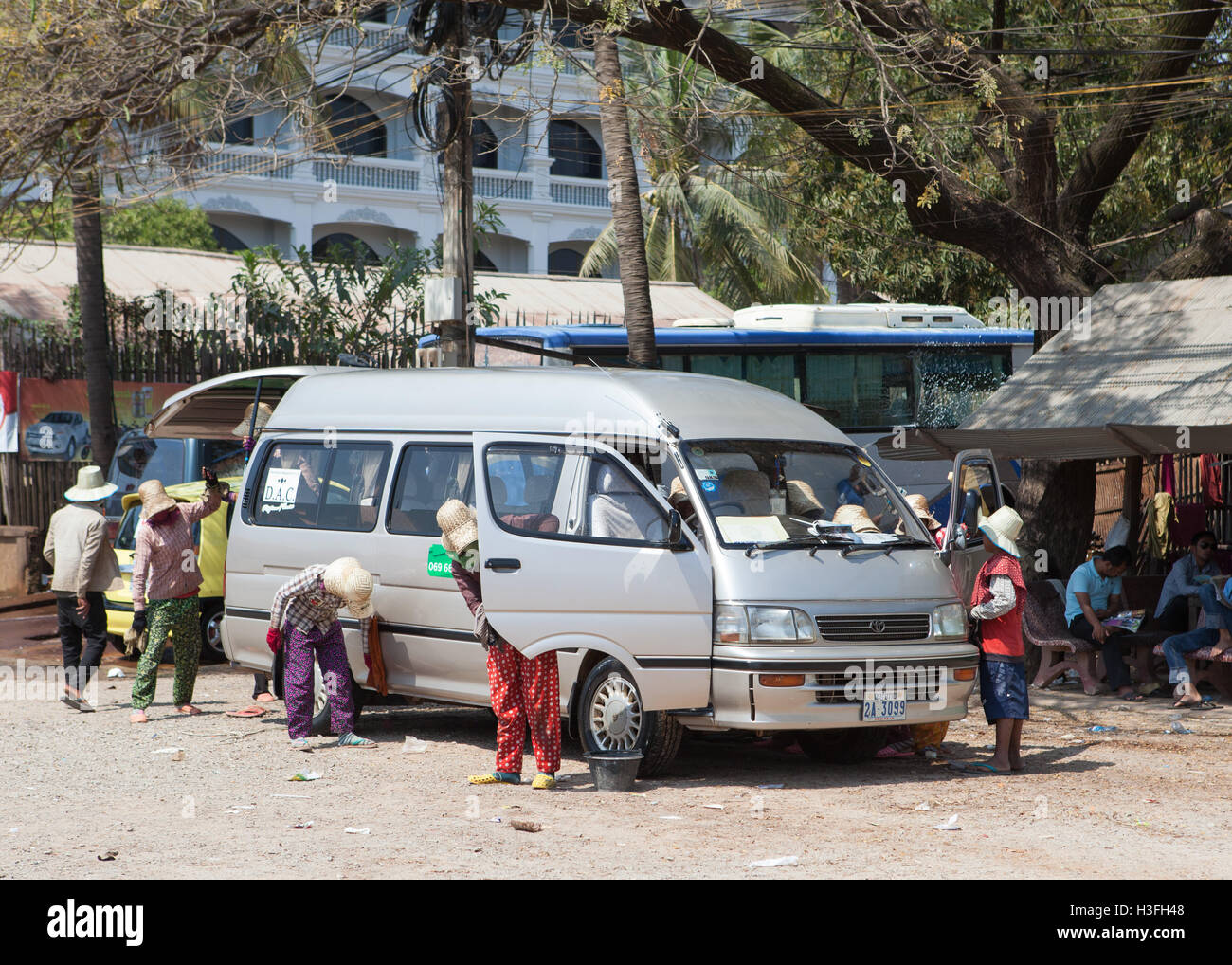 Women cleaning a minibus in Siem Reap,Cambodia. - Stock Image