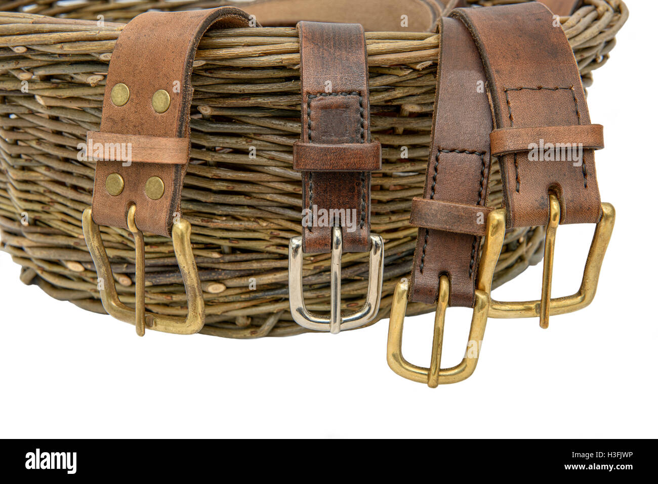 Handmade leather belts with metal buckles arranged over a hand woven willow basket. Isolated against a white background. - Stock Image