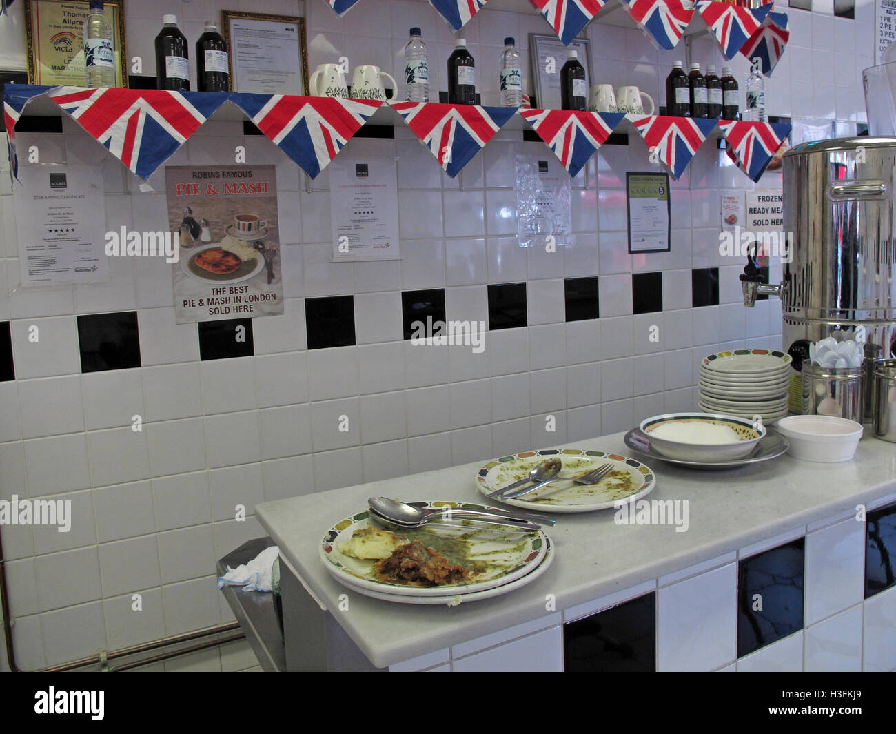 Inside Robins traditional Pie & Mash, Ilford Essex, Greater London, England, dirty plates - Stock Image