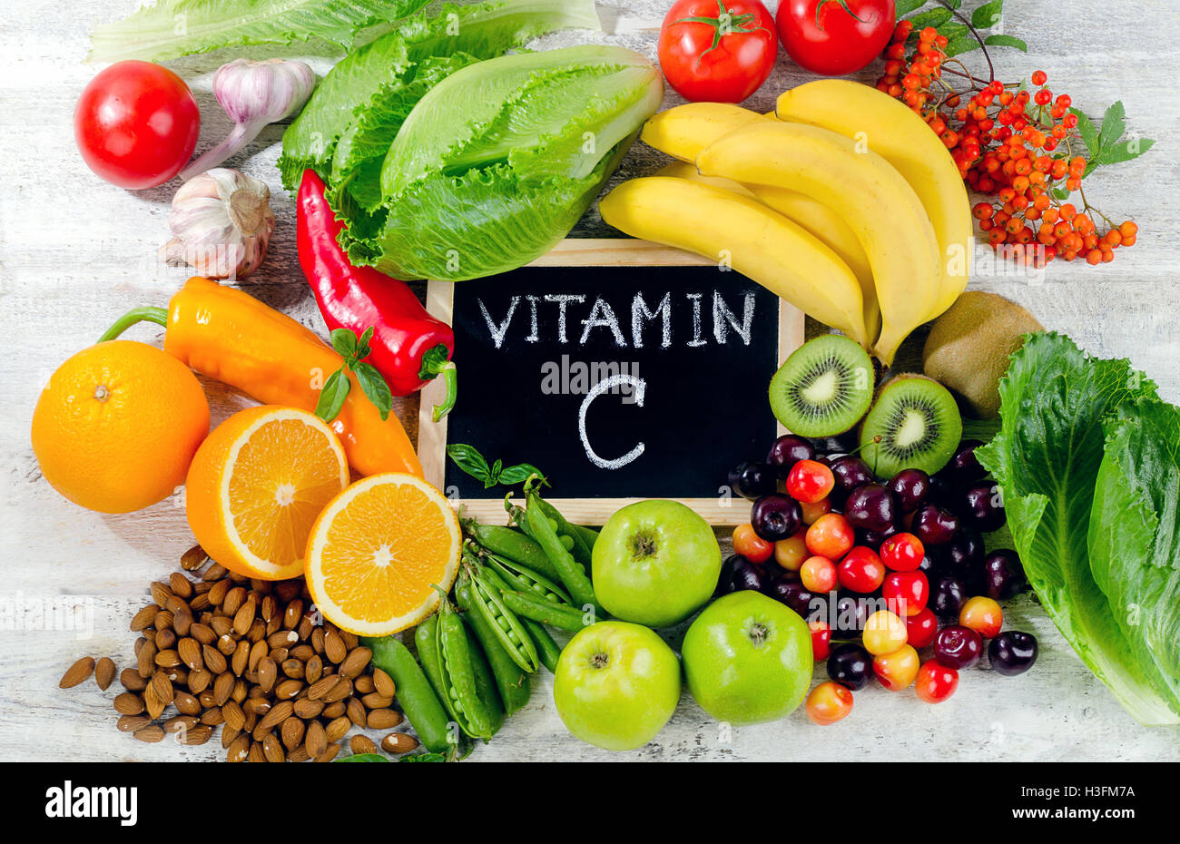 Foods High in vitamin C on white wooden board.  Healthy eating. Flat lay - Stock Image