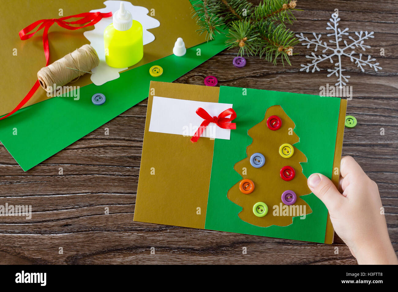 the child create christmas greeting cards paper festive fir in christmas tree toys glue scissors paper leaves thread on a w
