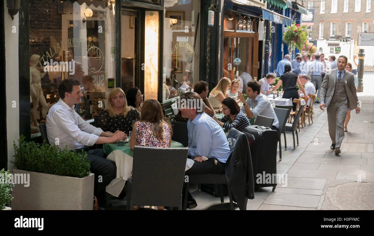 People relaxing at cafes at Shepherds Market  Mayfair London - Stock Image
