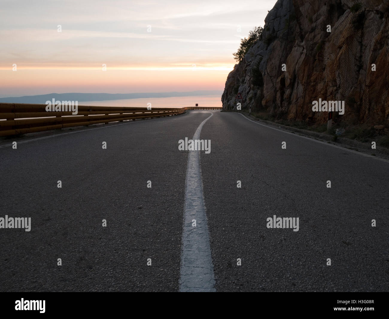 Asphalt mountain road above the sea at sunset - Stock Image