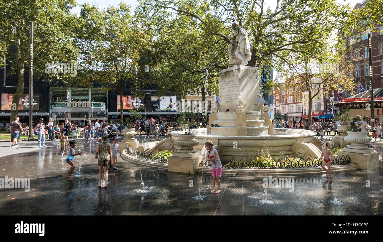 Children playing in the fountains at Leicester Square in central London - Stock Image