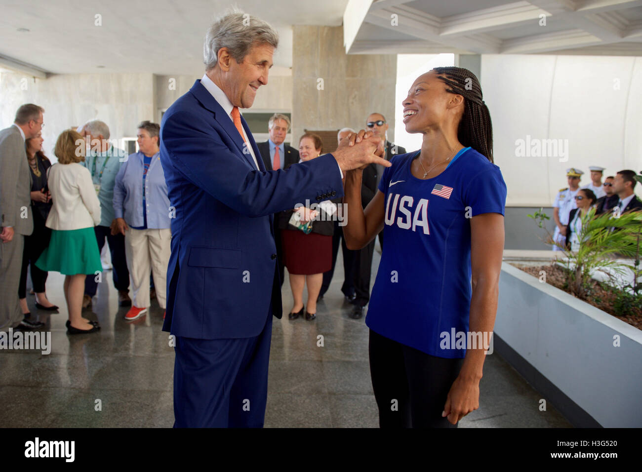 U.S. Secretary of State John Kerry clasps hands with Olympic gold medalist and track star Allyson Felix as he and - Stock Image