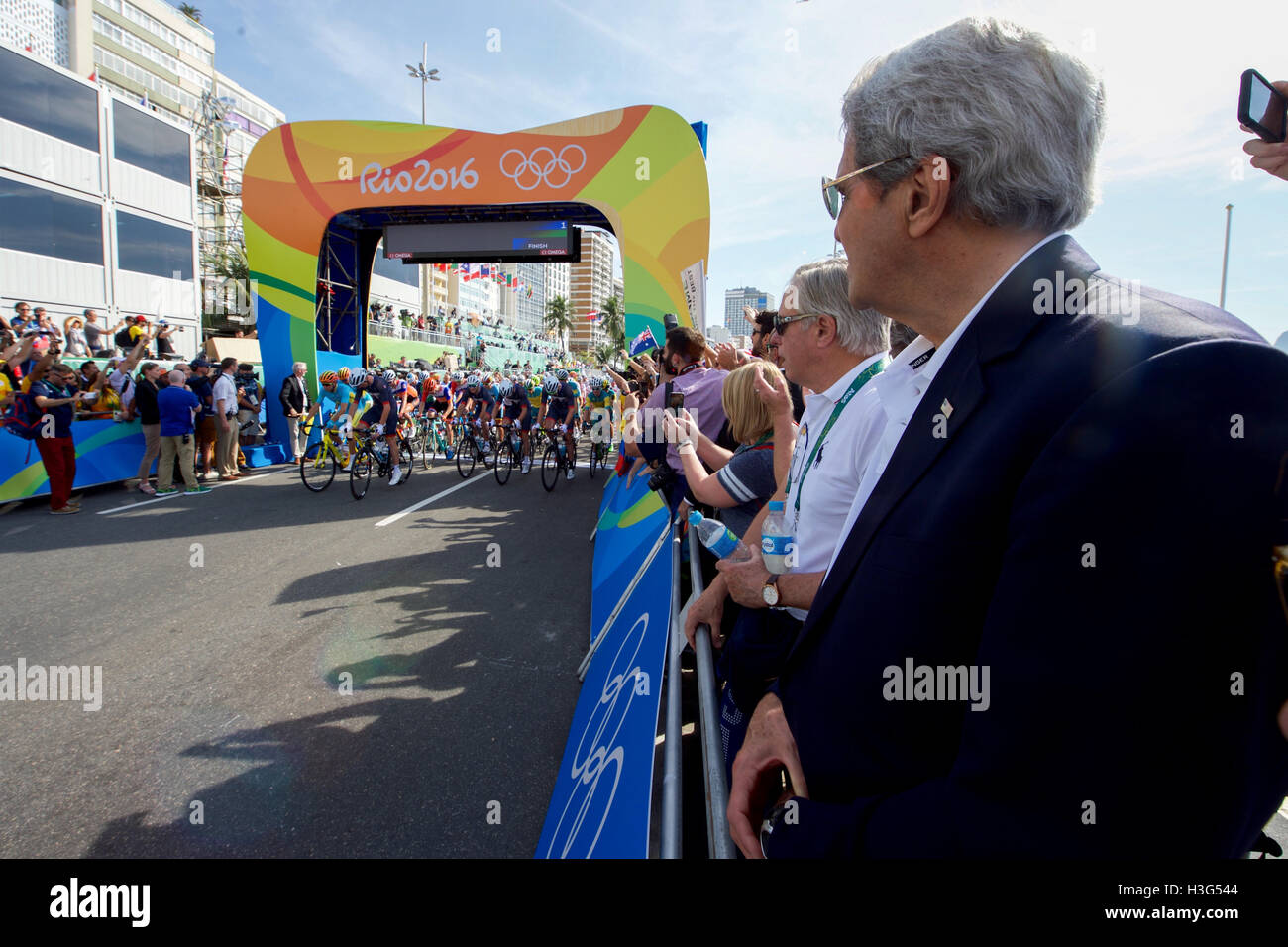 U.S. Secretary of State John Kerry watches the start of the Olympic men's cycling race along the Copacobana - Stock Image