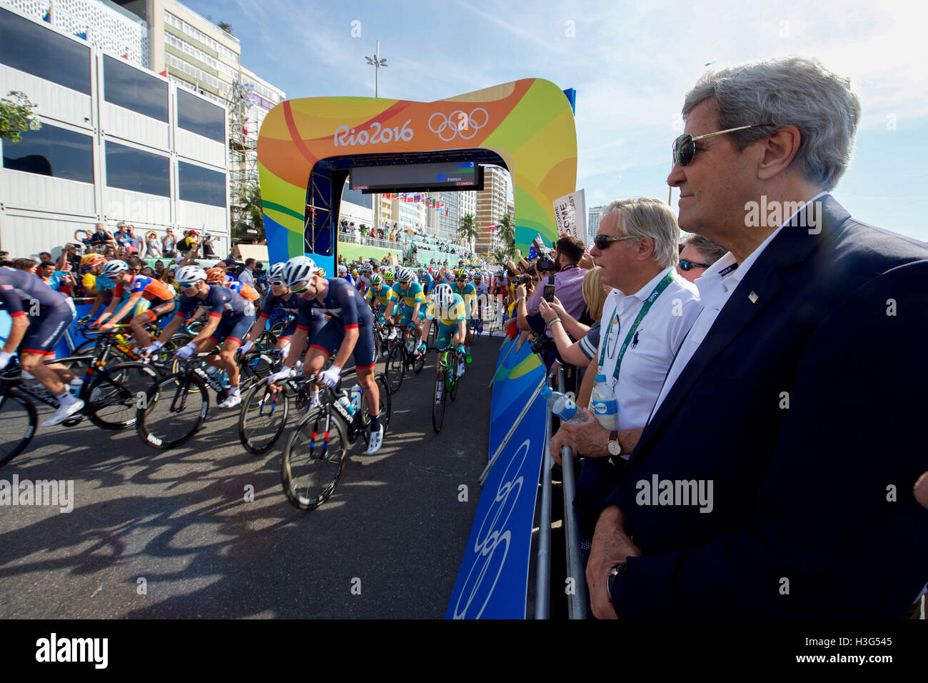 U.S. Secretary of State John Kerry watches the start of the Olympic men's cycling race along the Copacobana beach in Rio de Janiero, Brazil, as he and his fellow members of the U.S. Presidential Delegation attend the Summer Olympics on August 6, 2016. Stock Photo