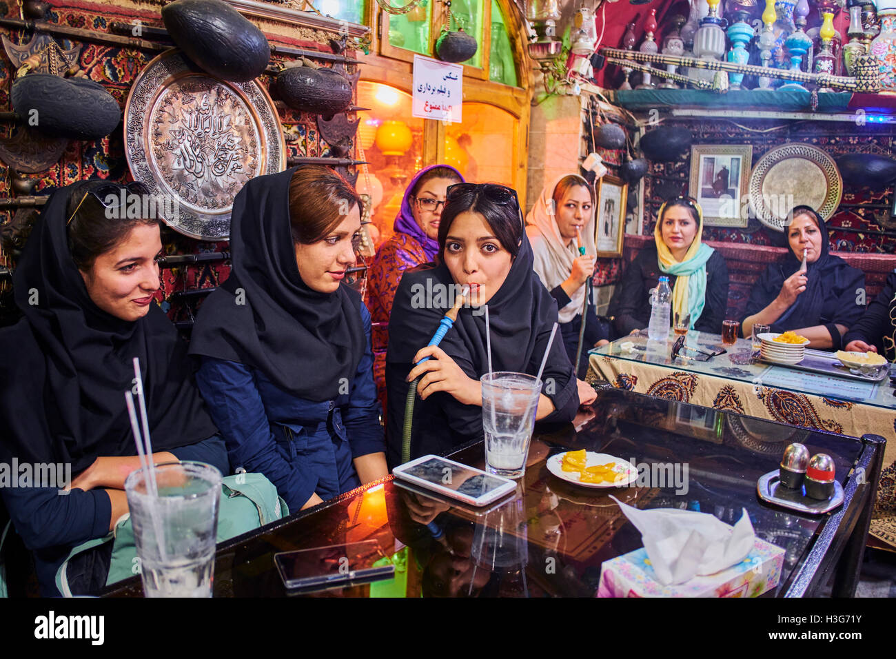 Iran, Isfahan, Azadegan teahouse, young women smoking a water pipe - Stock Image