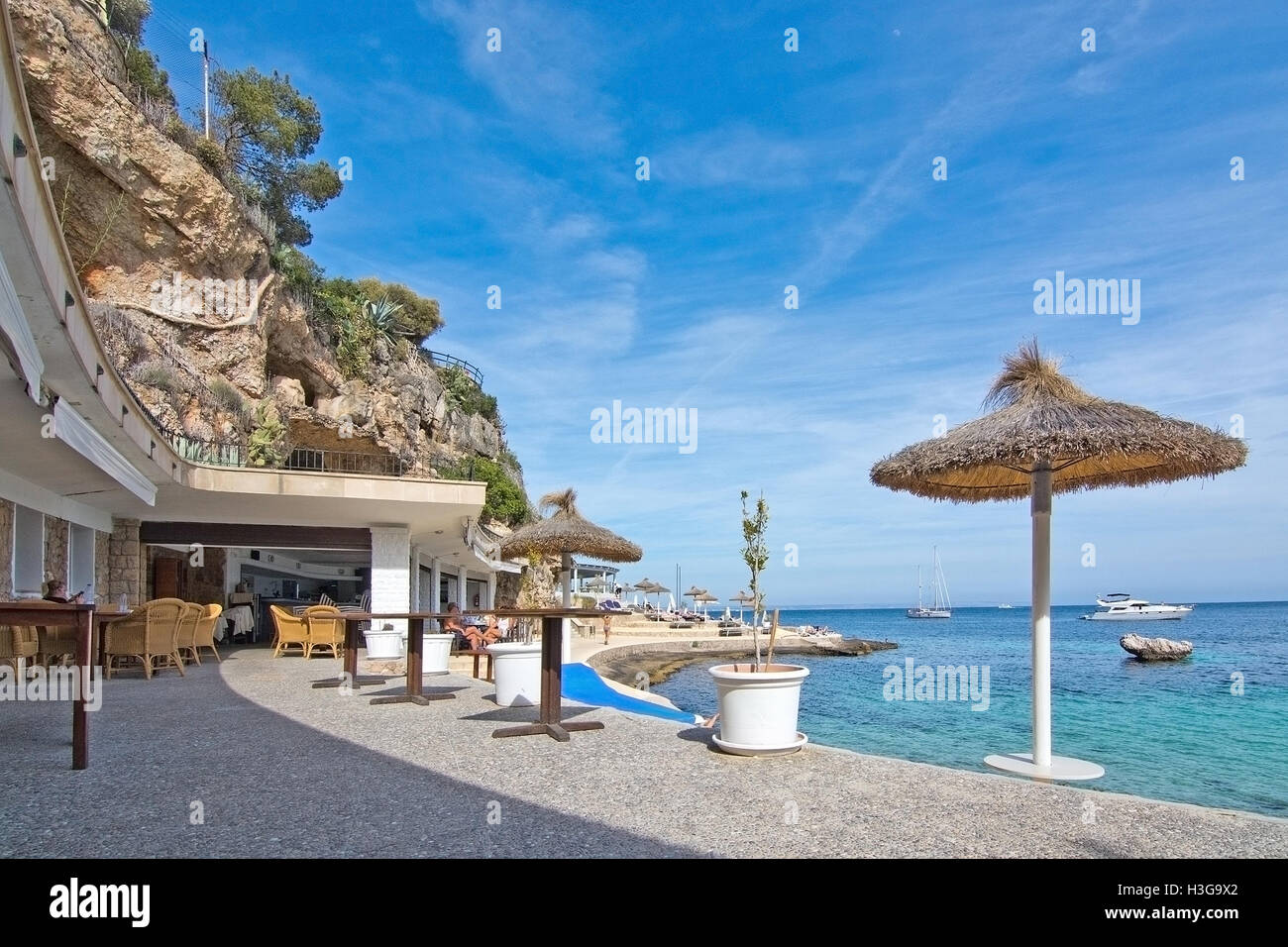 Beach bar and terrace with straw parasols and ocean horizon in Illetes, Mallorca, Spain on June 12, 2016. - Stock Image
