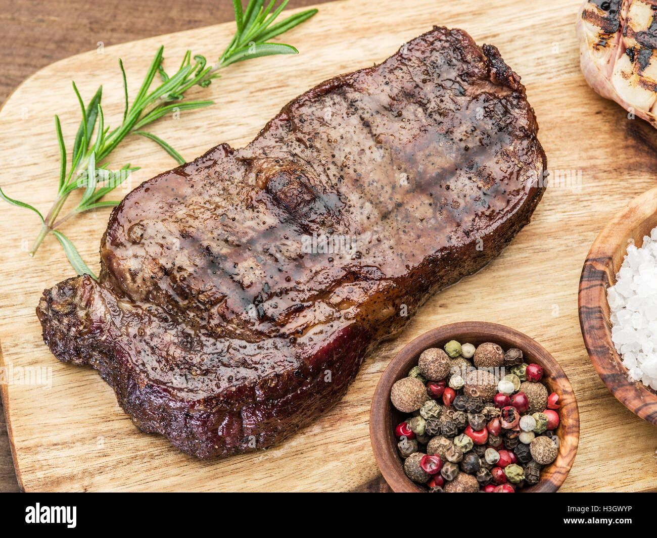 Steak Ribeye with spices on the wooden tray. - Stock Image