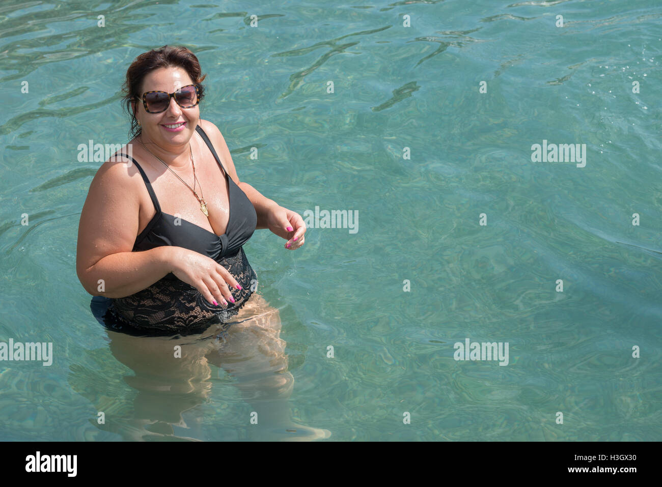full length portrait of plump mature woman in dark lace swimsuit