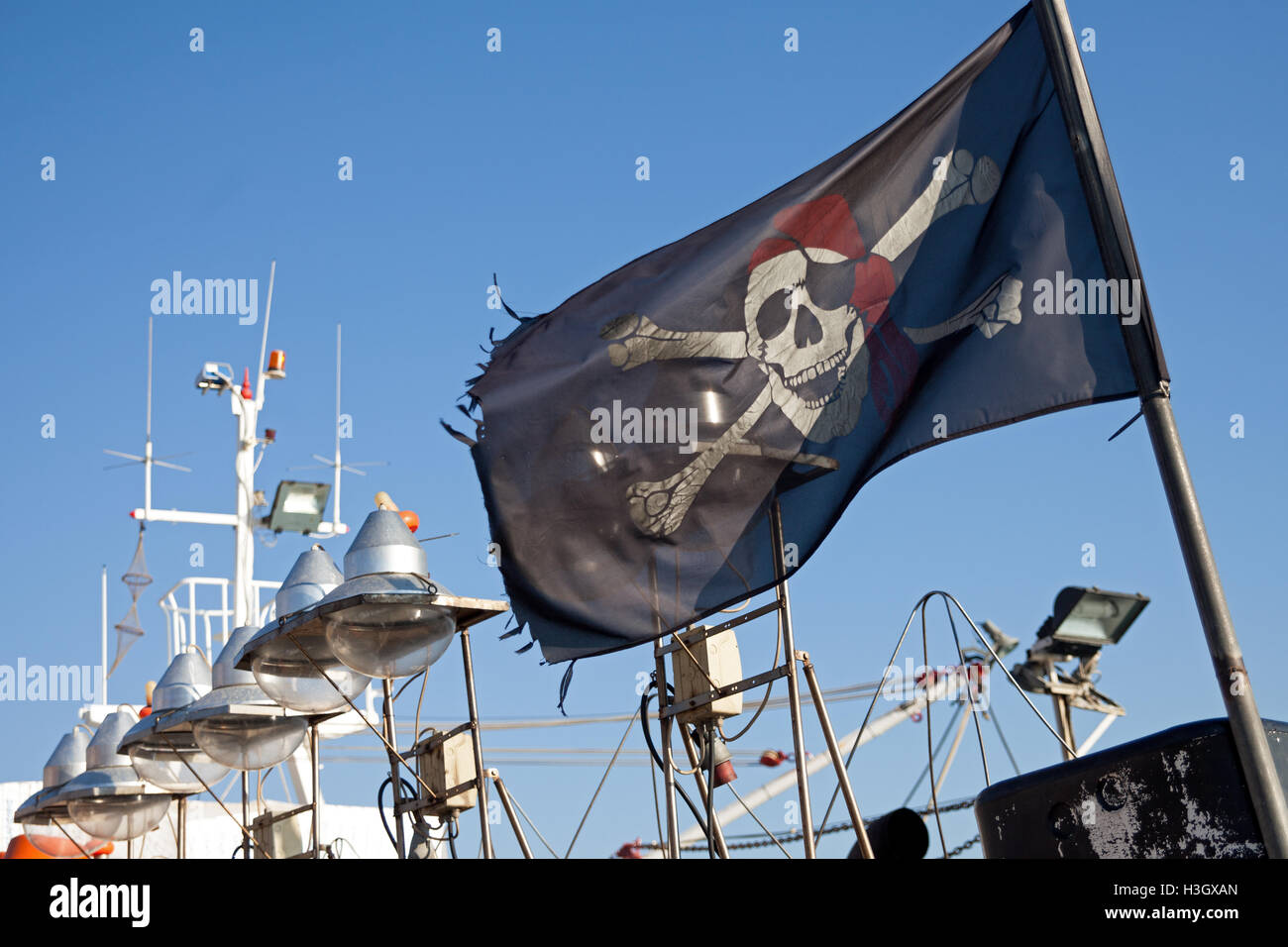 A fishing boat flying the jolly roger pirate's flag in Mithymna / Molivos in Lesbos / Lesvos in Greece. - Stock Image