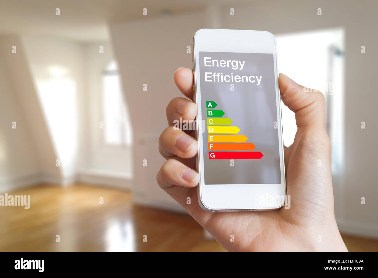 Energy efficiency rating on smartphone app by woman real estate agent and home interior in background - Stock Image