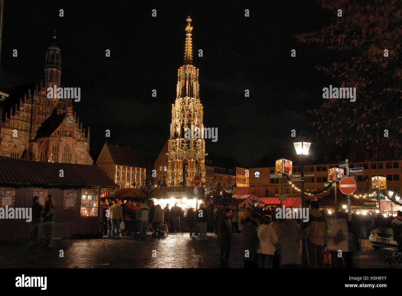 The flood lit 14th century, 19 meters tall  fountain, 'Schoner Brunnen' is permanently located in  the busy - Stock Image