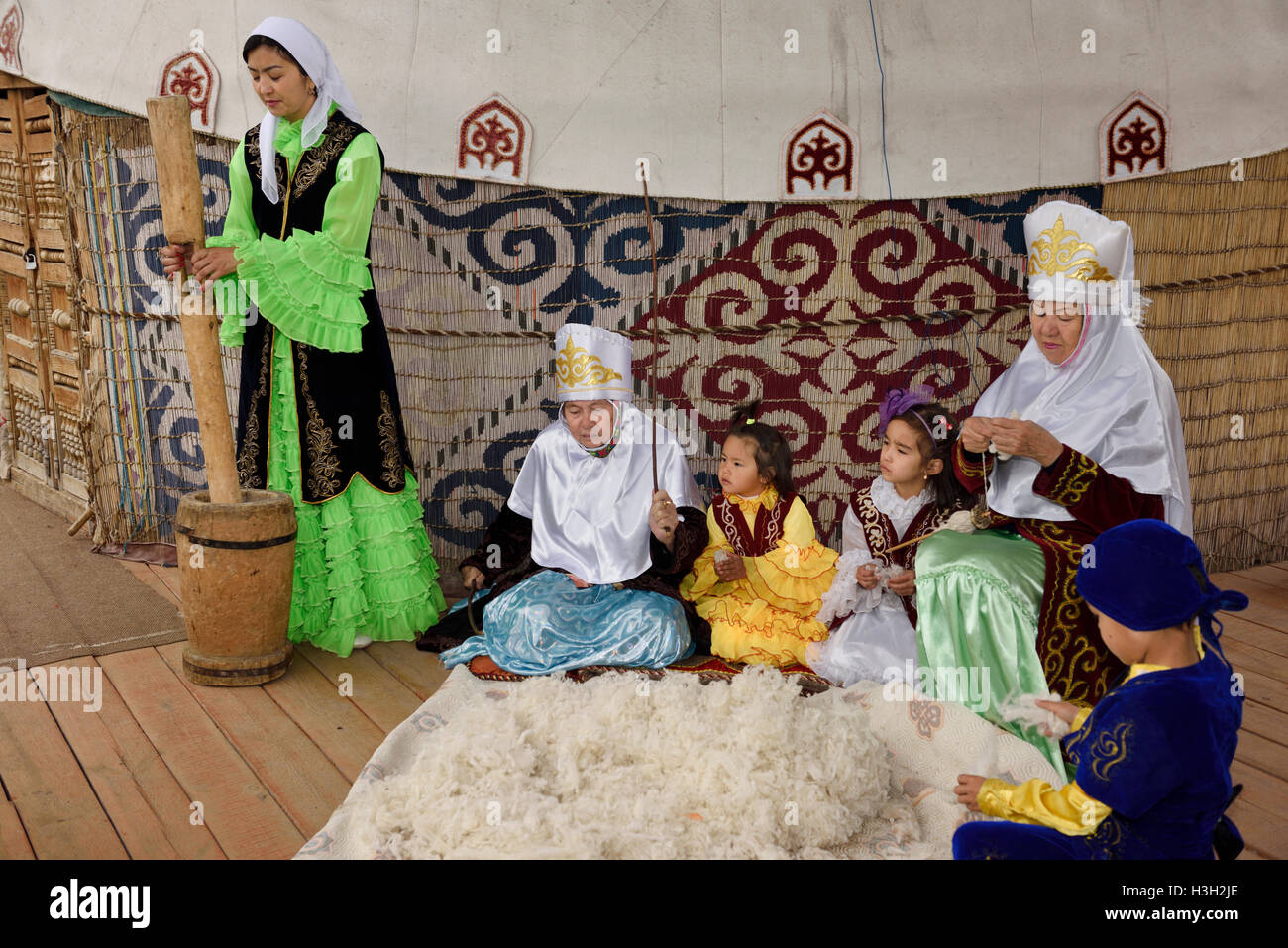 Family in traditional Kazakh clothes working wool into felt and yarn next to a yurt at Huns Village Kazakhstan - Stock Image