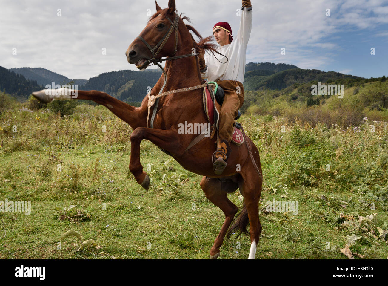 Kazakh horse rider raising arm on rearing gelding in Huns village Kazakhstan - Stock Image