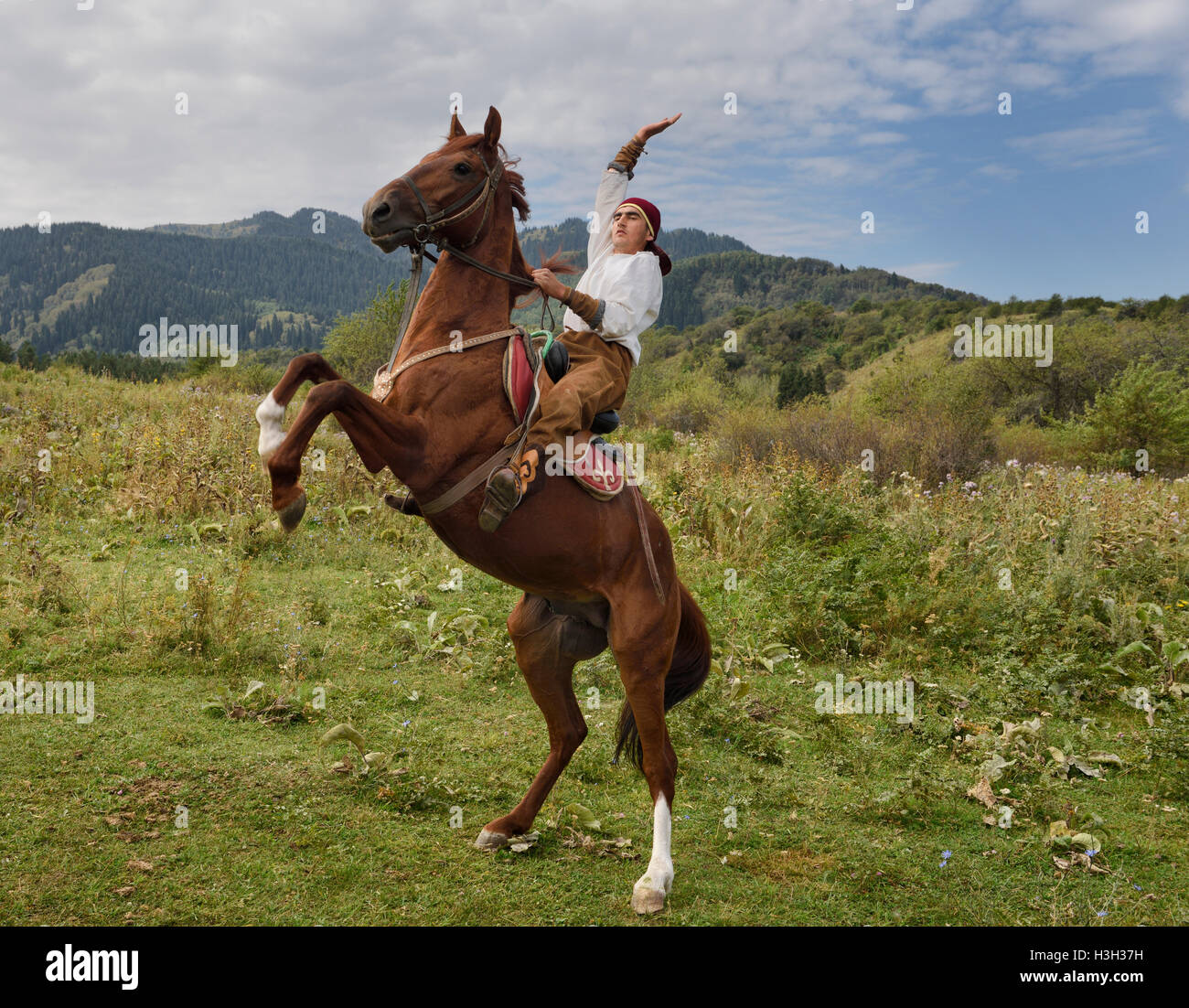 Kazakh horse rider with raised arm on rearing gelding in Huns village Kazakhstan - Stock Image