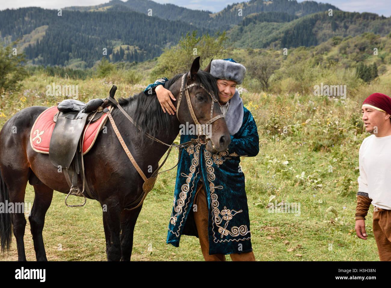 Man in traditional shapan overcoat and Borik cap hugging a stallion at Huns village Kazakhstan - Stock Image