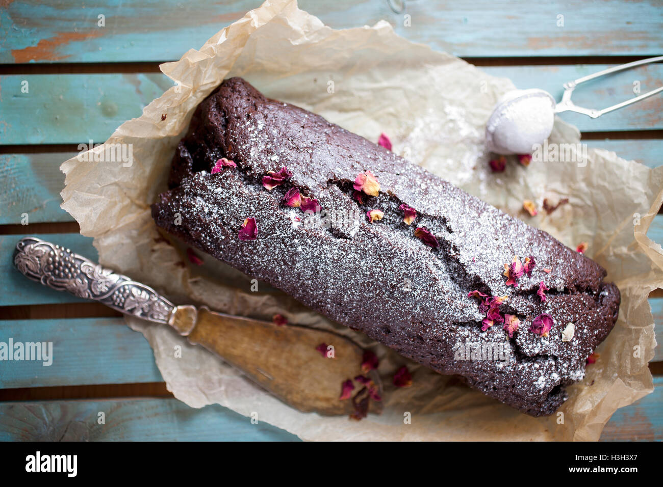 Homemade chocolate banana loaf with dried roses - Stock Image