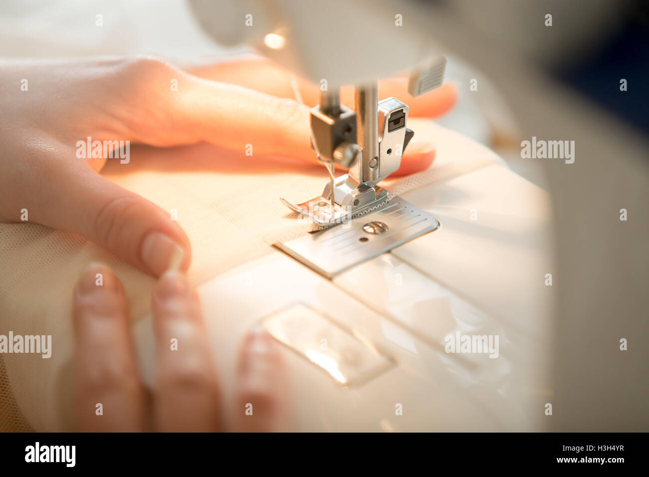 Hands at sewing machine - Stock Image