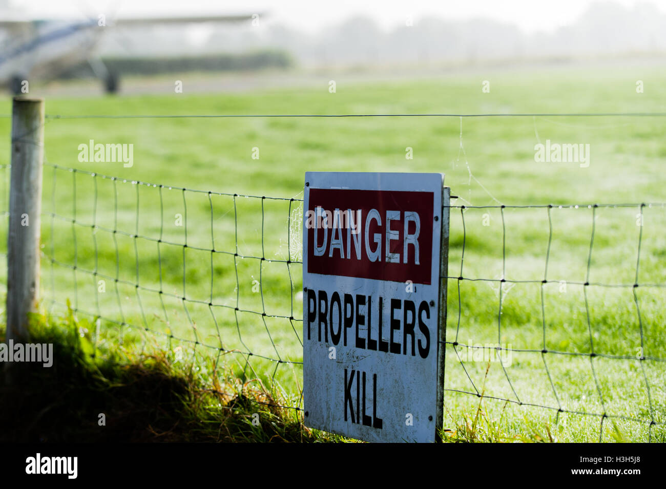 'Danger propellers kill' warning sign, with a Pilatus PC-6 Porter aircraft at the Irish Parachute Club in - Stock Image