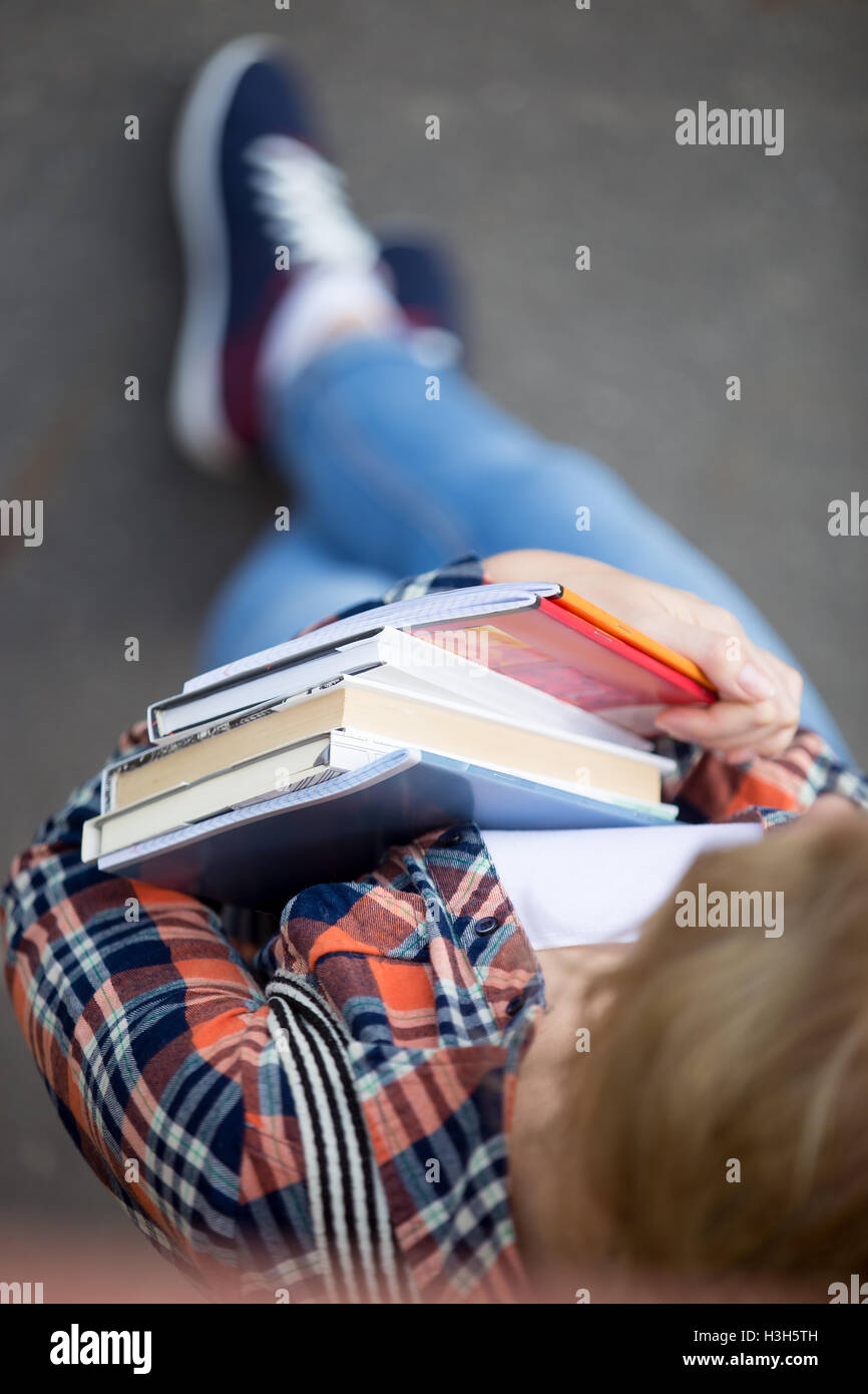 Student girl with a heap of textbooks and notebooks - Stock Image