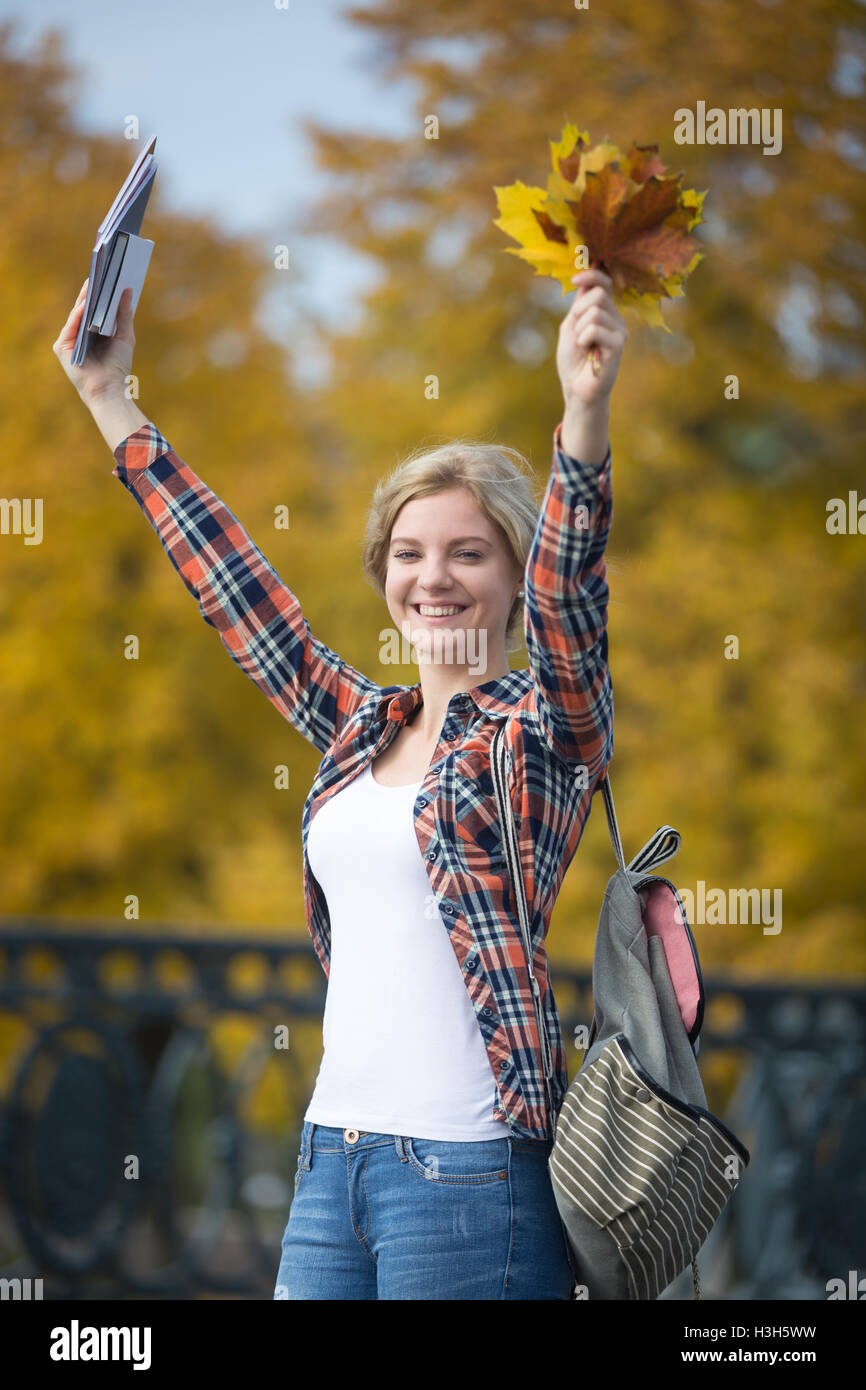 Portrait of smiling female young student outdoors holding yellow leaves - Stock Image