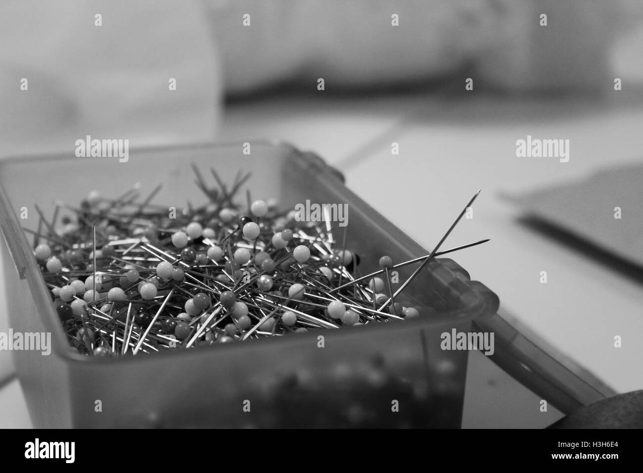 A box of sewing pins sits open on a table. - Stock Image