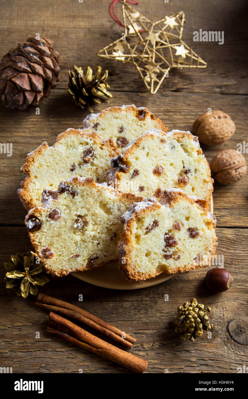 Christmas festive fruit bread (cake, fruitcake) on rustic wooden board with cinnamon and decor - homemade Christmas - Stock Image