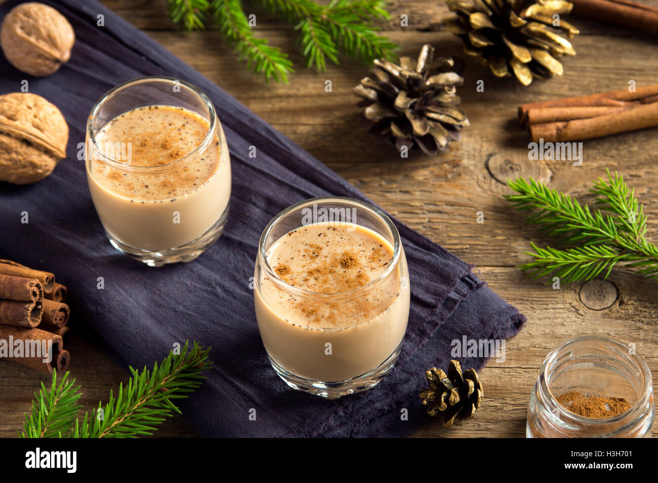 Eggnog with cinnamon in glasses over rustic wooden background with Christmas decor  - homemade Christmas festive Stock Photo