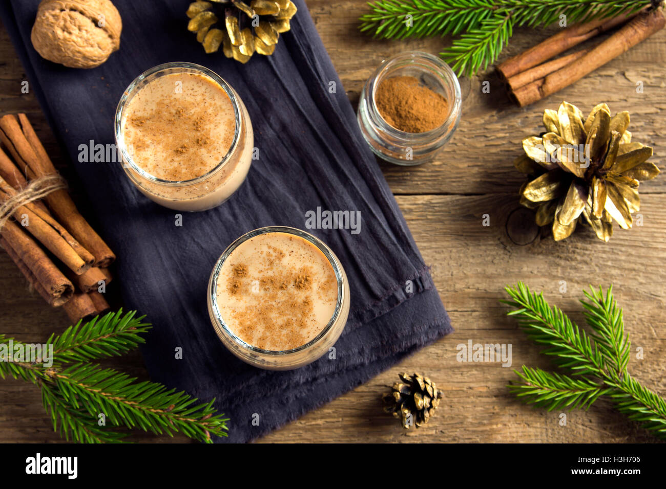 Eggnog with cinnamon in glasses over rustic wooden background with Christmas decor  - homemade traditional festive Stock Photo
