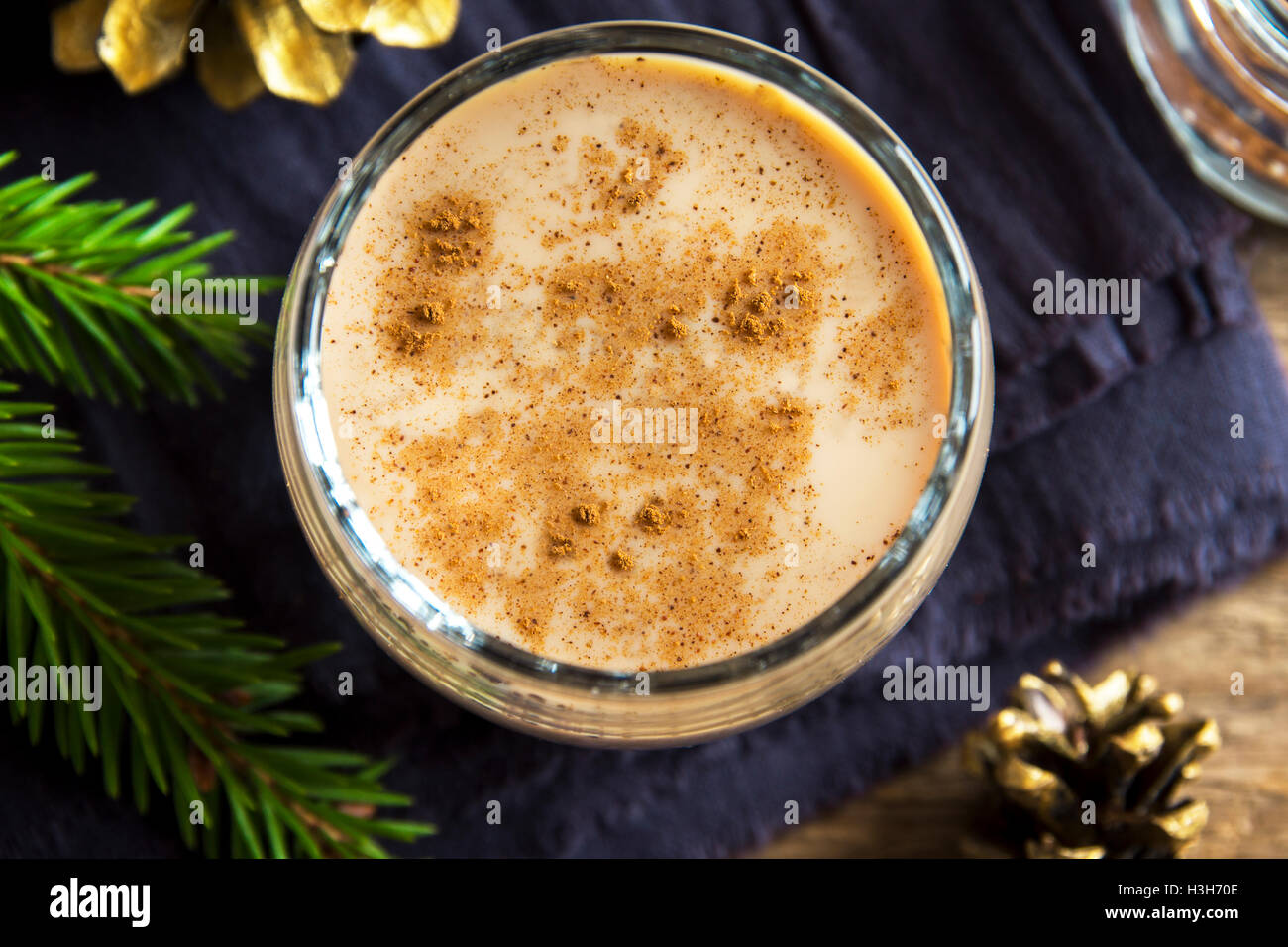 Eggnog with cinnamon in glass close up with Christmas decor  - homemade traditional festive drink for Christmas - Stock Image