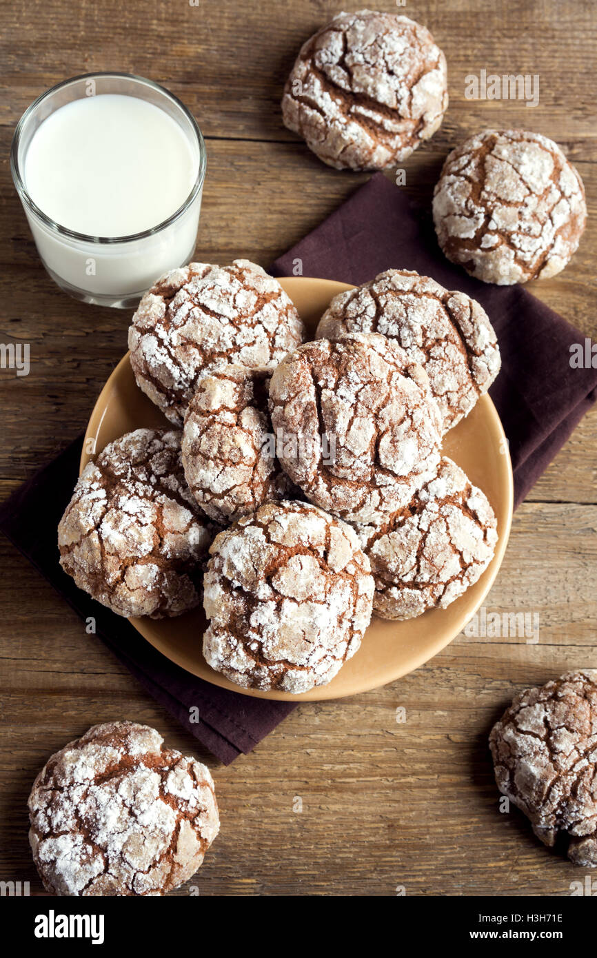 Chocolate crinkle cookies on plate with milk close up - homemade winter chocolate christmas pastry Stock Photo