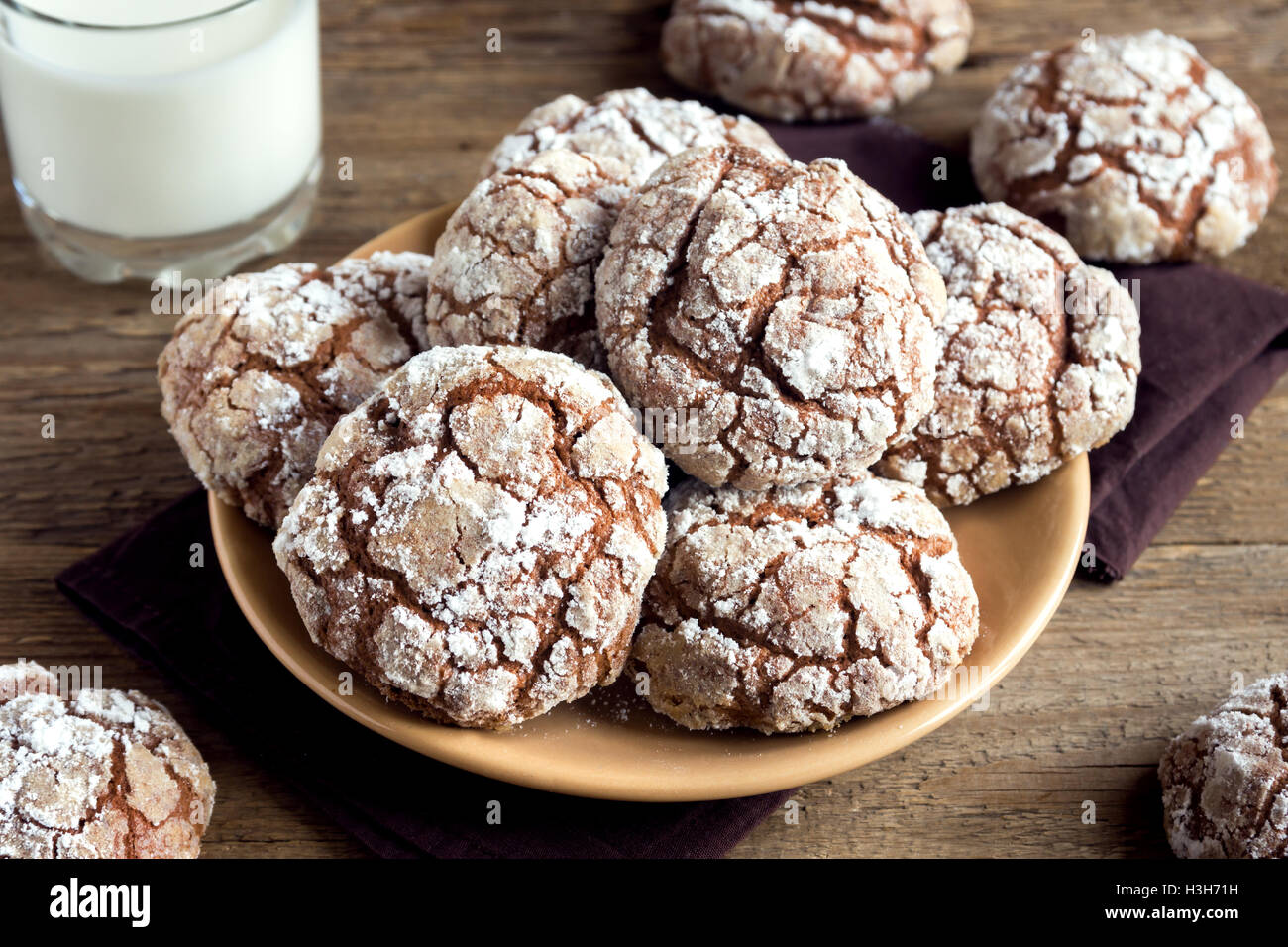 Chocolate crinkle cookies on plate with milk close up - homemade winter chocolate christmas pastry - Stock Image