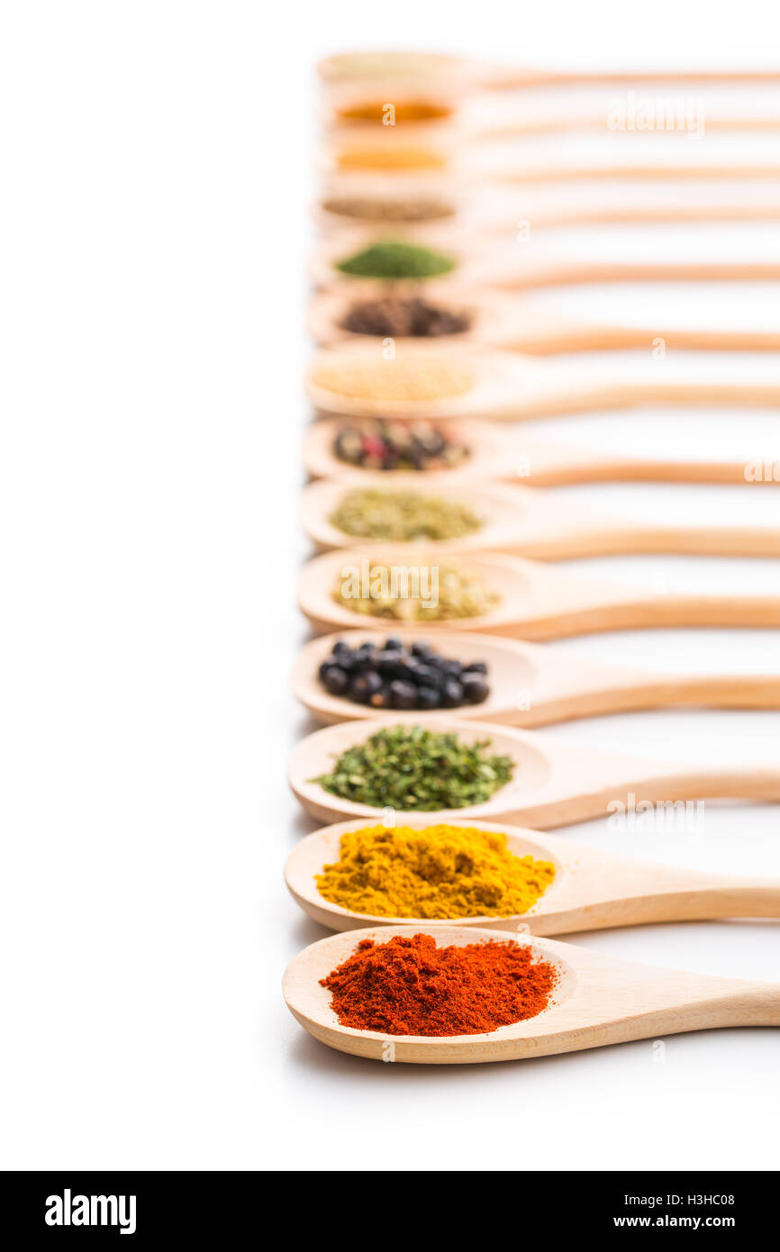 Various spices in wooden spoons isolated on white background. - Stock Image