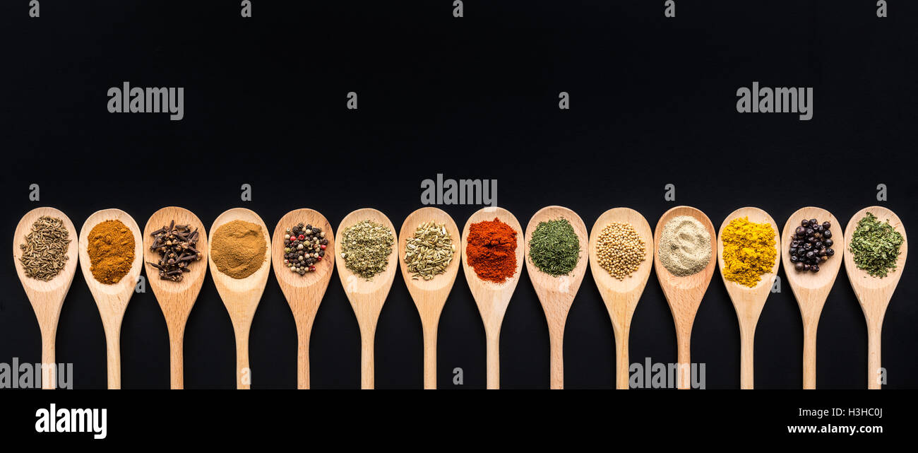 Various spices in wooden spoons on black background. Top view. - Stock Image