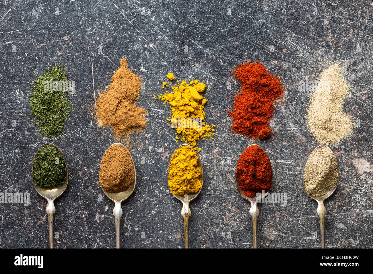 Various spices in spoons on old kitchen table. Top view. - Stock Image