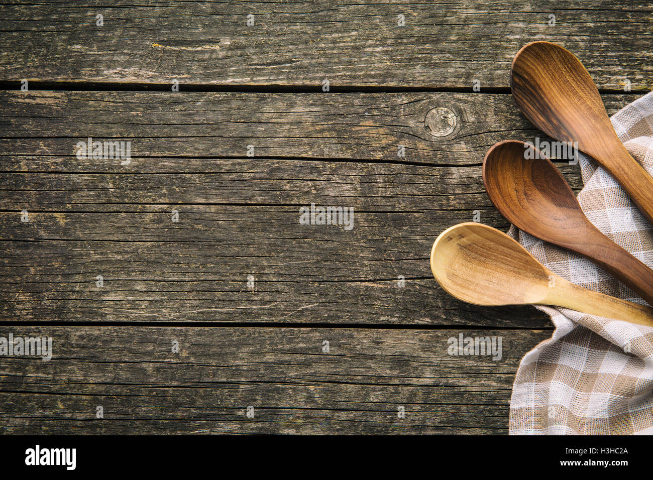 Handmade wooden spoons on old wooden table. Top view. - Stock Image