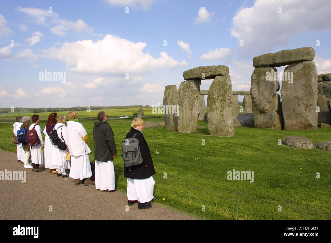 White robed visitors stand in awed silence in front of the 4600 year old sarsen stones of the neolithic monument - Stock Image