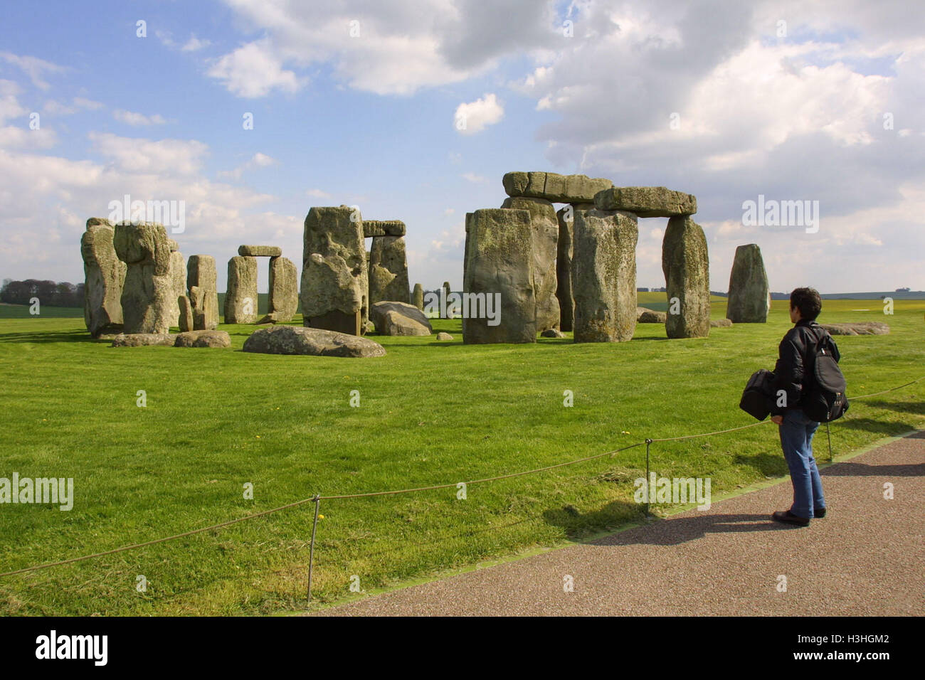 A visitor stands in awed silence in front of the 4600 year old stones of the neolithic monument Stonehenge in on - Stock Image