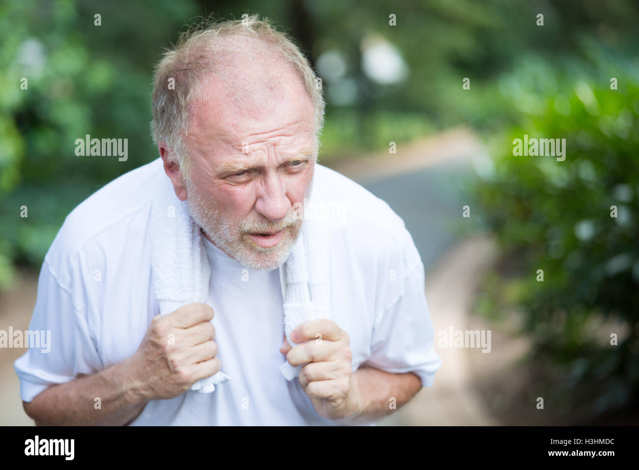 Closeup portrait, senior guy holding towel, very tired, exhausted from over exertion, sun stroke, isolated outdoors - Stock Image