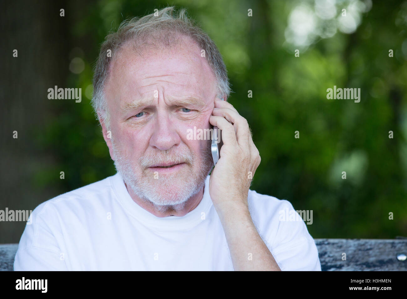 Closeup portrait, senior mature man in white t-shirt sitting on bench, having serious conversation on cell phone - Stock Image